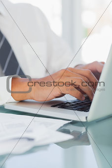 Close up on businessmans hands typing