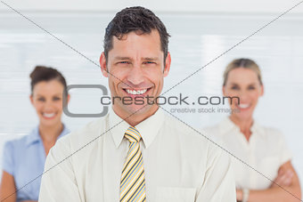 Smiling businessman posing with his colleagues on background