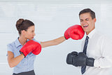 Businesswoman punching her colleague while boxing together