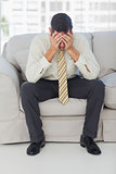 Troubled businessman sitting on sofa