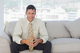 Self-confident businessman sitting on sofa