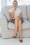 Thoughtful attractive businesswoman posing sitting on sofa