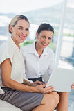 Cheerful attractive businesswomen working together