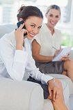 Businesswoman having a phone call while her colleague writing