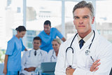 Experienced doctor posing with colleagues in background