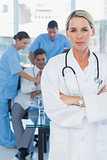 Serious blond doctor posing with colleagues in background
