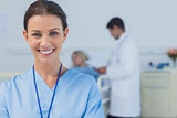 Cheerful surgeon posing with doctor attending patient on background
