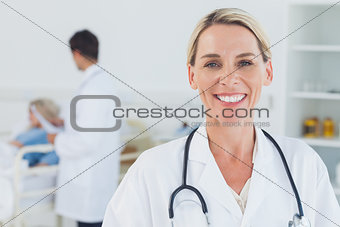 Smiling blond doctor posing with doctor attending patient on background
