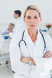 Serious doctor posing with doctor attending patient on background