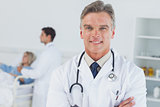 Experienced doctor posing with doctor attending patient on background
