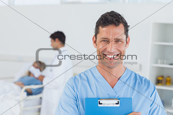 Portrait of surgeon with doctor attending patient on background