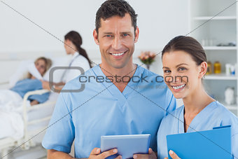 Portrait of surgeons with doctor attending patient on background