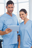 Smiling surgeons working together on tablet