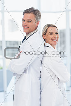 Experienced doctors posing together back to back