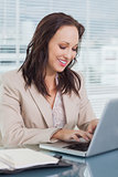 Smiling businesswoman typing on her laptop