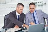 Serious businessmen working on their laptop