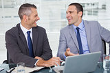 Cheerful businessmen laughing while working