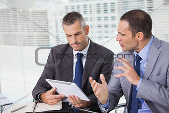 Serious businessmen analyzing documents on their tablet