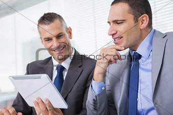 Smiling businessmen working together on their tablet
