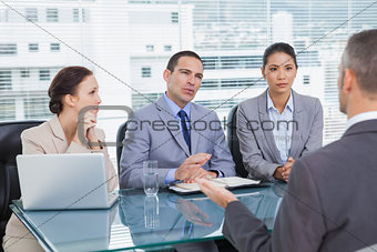 Serious business team interviewing experienced man