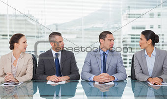 Business people sitting straight talking together