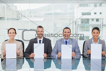 Smiling interview panel holding white paper