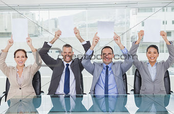 Smiling interview panel holding blank sheets above their head hiding the marks