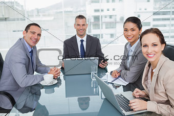 Smiling business people working together with their laptop