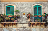 Beautiful vintage balcony with colorful flowers and doors