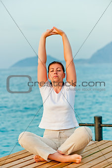 girl on the pier is engaged in gymnastics
