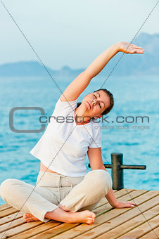 young woman engaged in Pilates by the Sea