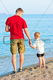 Father and son admiring the sea at sunset