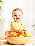 Little baby holding fresh fruits