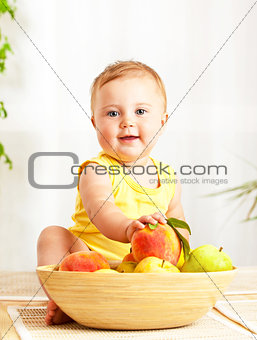 Little baby holding fresh fruits