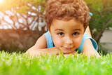 Baby boy lying down on green field