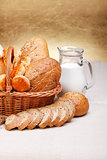 Bread products in basket and jug of milk