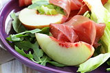 gourmet salad with peaches and bresaola (smoked beef)
