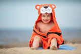 Cute little boy wearing tiger towel outdoors
