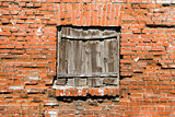 Blocked window on the red brick wall background.
