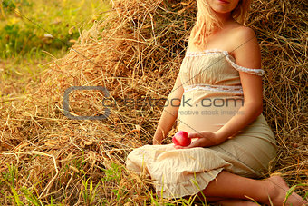 Pregnant woman on nature near the haystacks