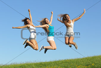 Group of three teenager girls jumping on the grass