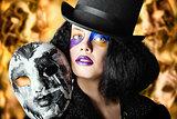 Female jester holding carnival mask. Halloween fete