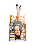 Cute young woman sitting upside down on chair