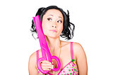 Young woman barber holding large pink scissors