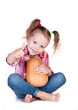 Little girl with pumpkin thumbs up