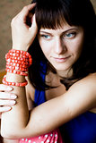 Portrait of a beautiful young brunette with red beads