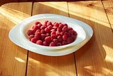Raspberries in plate on the wooden table