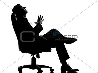 one business man sitting in armchair relaxing thinking silhouett