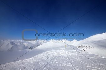 Warning sing on ski slope and snowy mountains in haze