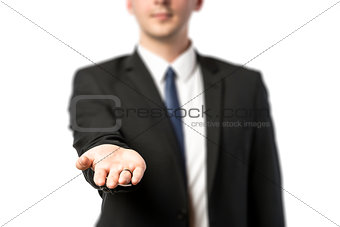 Businessman in dark suit holds out his hand flat